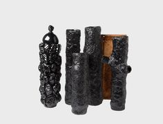 A collection of moody black sculptural objects with plenty of unexpected texture and glassy surfaces that are created from insect waste.