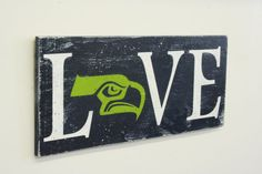 Seahawks fans will love this! This is a wood sign that measures 18 x 8. The background is Navy. Letters LVE are White and seahawk design is