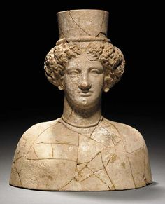 A GREEK TERRACOTTA BUST OF A WOMAN   Hellenistic Period, Circa 300-250 B.C.   Perhaps depicting Persephone, the beautifully-modelled face with heavy-lidded eyes, full lips and a dimpled chin, her thick, center-parted wavy hair supporting a cylindrical polos, the earlobes perforated for now-missing earrings, wearing a molded necklace with beech-nut pendants, the plain bust with rounded shoulders, the breasts only slightly modelled, preserving traces of white pigment throughout