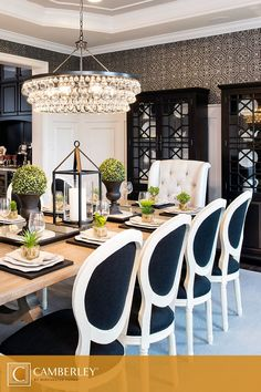 A supremely elegant crystal chandelier hangs above the Hamilton model's formal dining room. Nature inspired centerpieces decorate the lightly stained wood dining table, making room feel fresh and open. Navy blue dining chairs and button-tufted chairs at the heads of the table, plus dish cabinet displays showcasing delicate china, give this room a truly regal aesthetic. #InteriorDesign #Camberley
