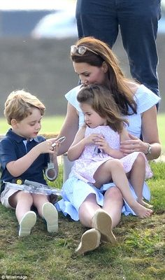 The Duchess of Cambridge cradles a barefoot Princess Charlotte in her lap while Prince George amuses himself with a set of toy handcuffs