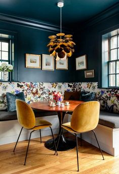 Corner nook / dining space with a built-in banquette (upholstered in a happy butterfly covered fabric), wooden round table and beautiful yellow chairs | Dark blue walls, yellow, white, brown.