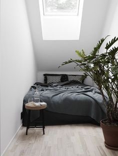 Minimal bedroom tucked into a sloped ceiling