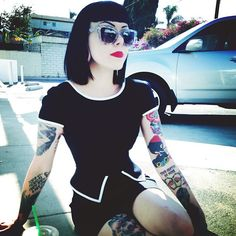 Very modern in black and white with inked arms. Blunt black hair and red lips.