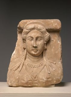 Limestone Bust from a Funerary Relief  Egypt, mid-2nd century A.D. H. (preserved): 31.0 cm (12 3/16) Gift of Frederick Stafford, 60.14 This architectonic relief shows a woman with her hair parted in the middle, swept back from her face and falling in long spirals down her shoulders. She wears a V-necked stola, earrings, a necklace, and offers a hint of a smile. Such idealized portraits, characteristic of funerary art in Roman Egypt, are known mainly from Alexandria and its surrounds.