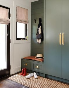 Transitional mudroom designed with hunter green cabinets on green shiplap trim.
