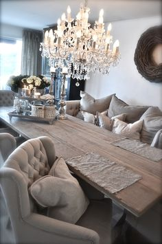 love the old farmhouse style table especially when combined with the comfy tufted seating (LOVING the armchair/sofa combo)--all tied together beautifully with the chic chandelier~