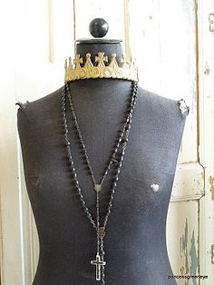 black mannequin with religious necklaces