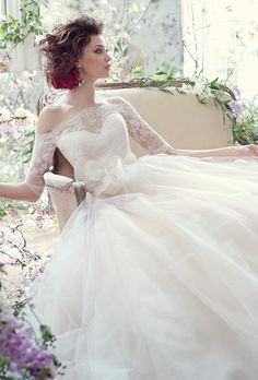 Sherbert tulle ball gown with sweetheart neckline, Alencon lace off the shoulder overlay with three-quarter sleeves, horsehair belt at natural waist, horsehair hem detail, chapel train. Brides: Tara Keely