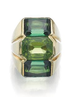PERIDOT AND TOURMALINE RING, ATTRIBUTED TO SUZANNE BELPERRON, CIRCA 1970.  Set to the centre with a cut-cornered rectangular mixed-cut peridot, flanked above and below with two step-cut tourmalines, size 531/2, French assay mark.