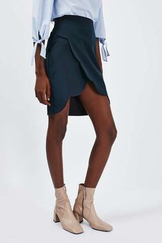 We're all about the details of this casual-cool skirt. In a navy blue hue, this skirt comes in a wrap style with pretty scallop detail. We love it styled with an off-shoulder blouse and nude ankle boots. #Topshop