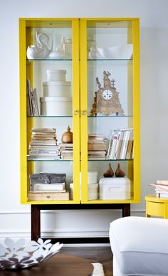 Vitrina STOCKHOLM en amarillos llena de cajas, libros, reloj, figuras decorativas, fabricada por IKEA