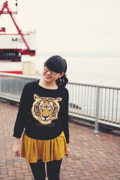 JennifHsieh Outfit | Black Tiger Bow Tie Print Sweater, Mustard Skirt, Black Tights, Black Thick-Rimmed Glasses
