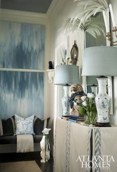 Vintage chinoiserie-style console lamps and a custom table skirt continue the color scheme, as do a set of abstract paintings and a gallery wall of silver leaf–framed intaglios, which complement the high ceilings without overpowering the room.