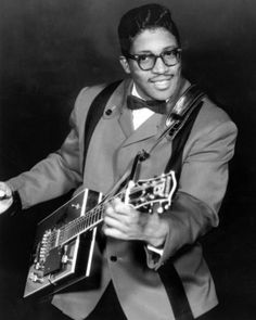 """Bo Diddley - In 1928, one of America's most influential blues musicians, Ellas Bates -- better known as Bo Diddley -- was born to a desperately poor couple in rural Mississippi. At a young age, he was adopted, along with three cousins, by his mother's cousin, who moved the family to Chicago in the mid-1930s. Diddley, nicknamed """"The Originator,"""" would go on to record nearly 40 records and be inducted into the Rock and Roll Hall of Fame in 1987."""