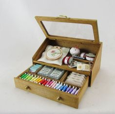 A sloping lidded box containing a wide variety of haberdashery item.  Ribbons, threads, pin cushion, hoop the list goes on and one.