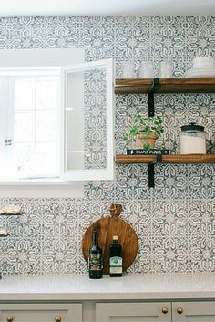 Gorgeous patterned tile backsplash with bracketed wood open shelves and marble kitchen counter tops.