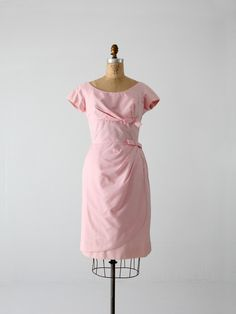 A chic 1950s vintage cocktail dress. The elegant pink dress features draped pleating that gathers to the left side on the bust and waist. This creates an illusion of a wrap skirt with a draped front p