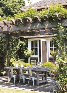 Pergola with vine over dining area. White windows and trim, dark siding, wood pergola, large gray pavers Outdoor Areas, Outdoor Rooms, Outdoor Dining, Dining Area, Outdoor Tables, Rustic Outdoor, Rustic Table, Patio Dining, Dinning Chairs