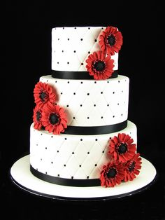 Quilted white wedding cake with black trim and piped dots and my hand made burgundy gerberas to match the bridal flowers. Top and bottom tiers are chocolate mud cake with milk chocolate ganache. Middle tier is vanilla buttercake with raspberry jam and white buttercream. At the reception I added a spectacular batman topper provided by the bride. Check out my page at www.facebook.com/cakesbyleannerhodes