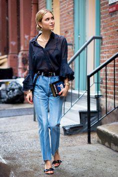 Pernille Teisbaek of Look De Pernille wears a black sheer shirt with flare sleeves, denim mullet jeans and black heels.