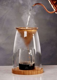This pour-over coffee maker is designed to elevate the ritual of making coffee by hand. Hot water is gradually poured through fresh ground coffee in a filter, and brewed coffee slowly drips into the carafe, or a mug. The slower extraction speed better develops natural sweetness and balances the sparkling acidity of a light-roasted coffee. It's non-toxic and food safe, with easy-to-read measurements on the carafe for accuracy.The handmade sculptural glass form provides full visibility of…