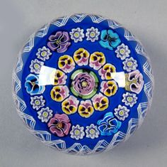 """Parabelle glass, Artist Proof 1998. Center pink Clichy-type rose, circle of yellow and white pansies. Outer circle includes multiple colors of Parabelle's trademark pansy canes. Twisted latticino edge. Royal blue ground. 3 1/2'"""" X 2 1/2"""""""