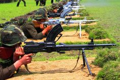Korean People's Army (KPA) officers and soldiers fire their weapons during an event marking the 64th anniversary of the start of the Korean War, Wednesday, June 25, 2014, in South Hwanghae Province, North Korea.