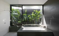 In this modern bathroom, there's a built-in bathtub that sits beside the shower. A window that opens to the garden makes it feel like you're showering outside. Black White Rooms, Black Walls, Bathroom Styling, Bathroom Interior Design, Interior Ideas, Dark Elements, Garden Bathtub, Garden Bathroom, Zen Bathroom