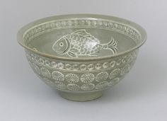 "A Korean Celadon Fish Bowl, ca. 19th Century. Green glaze ground on earthenware footed bowl with two-tone pigment decoration of fish. Approx. 5-3/4""T x 11"" diameter. Unsigned."