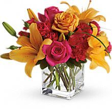 Orange asiatic lilies, hot pink and light orange roses, miniature red carnations and a bit of understated greenery.