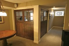 """Private basement gaming/media room ~ """"The two rustic cherry walls seen here are in their closed position. When open the fully tuck into pockets in the walls, thus opening up the gaming area to the rest of the basement."""" ~ kuhldesignbuild.com"""