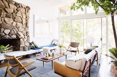 Mid Century Modern living room. Love that stone fireplace, the sofa and all the glass