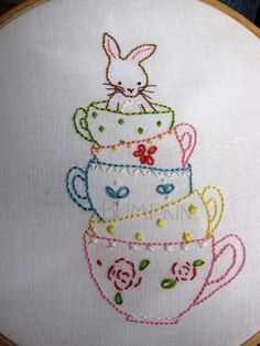 A towering stack of completely cute stitched tea cups complete with a darling bunny popping out of the top. #cute #stitchery #sewing #teacups #Easter #bunny #rabbit