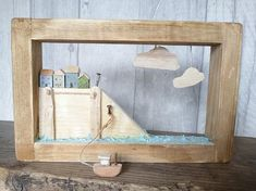 Made entirely from reclaimed wood, this coastal style shadow box creation has four tiny wooden cottages side by side on a stormy harbour wall. Realistic waves lap the harbour and a tiny wooden tugboat bobs about below. A little striped flag blows in the breeze of this shadow