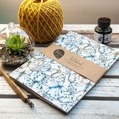 A5 recycled notebook featuring my original print design Butterfly Scatter, with lined paper inside. Made in the UK.  This notebook features sketched butterflies in a tones of blue, teal and ochre. A nature inspired gift perfect for a range of occasions from birthdays or a treat to yourself.  The cover is made from a thick recycled white card, which gives a very natural matt finish. Inside there are 48 lined pages and the notebook comes wrapped in a kraft paper belly band.  FSC Certified…