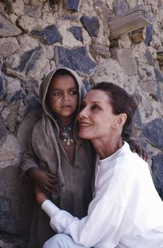 UNICEF Goodwill Ambassador Audrey Hepburn hugs a small girl who is standing in the shade of a large stone wall in the town of Mehal Meda in the northern part of the province of Shoa, Ethiopia. In 1988, internationally known film actor and UNICEF Goodwill Ambassador Audrey Hepburn travelled to Ethiopia on her first official UNICEF mission, to raise awareness of the impact of the continuing drought on the country's children and women. © UNICEF/NYHQ1988-0194/John Isaac http://www.unicef.org
