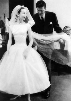 Audrey Hepburn being fitted by Hubert de Givenchy in the wedding dress he made for her to wear in Funny Face, Paris, 1956