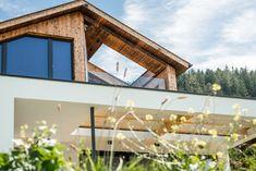 Die Fassadengestaltung des Einfamilienhauses zeichnet sich durch die Ausrichtung der Fenster aus, welche an die Ausblicke auf die umliegende Berglandschaft angepasst ist. Das Haus spiegelt dadurch eine Transparenz wieder, was der Idee eines offenen Lebensstils und einem gefühlvollen Umgang mit der Natur nahekommt. Im Herzen des Hauses werden alle Stockwerke durch eine offene Deckenkonstruktion miteinander verbunden, was im Innenraum ein Atrium entstehen lässt. Atrium, Cabin, House Styles, Home Decor, Room Interior, Windows, Mountain Landscape, Detached House, Environment