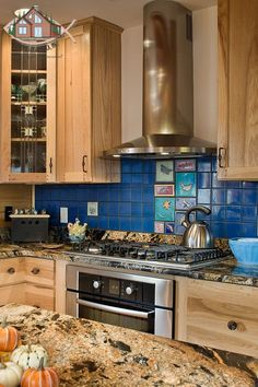Who says you can't do that colorful tile backsplash and modern range hood in your log home?