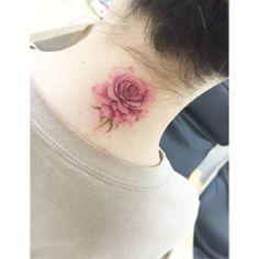 Tatuaje de una rosa de estilo acuarela en la nuca. Artista...