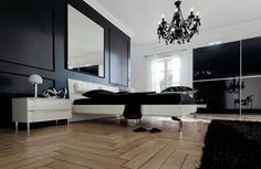 black walls, huge mirror, corked tile flooring & an elegant black chandelier