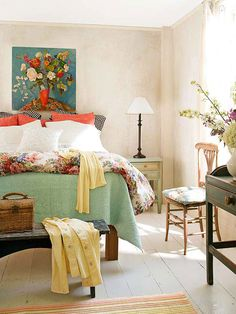 Subtle texture on the walls and a matelasse coverlet in this master bedroom make a soft backdrop for bright motifs in an original oil painting and a floral cotton duvet cover. A weathered bench at the foot of the bed is a gre