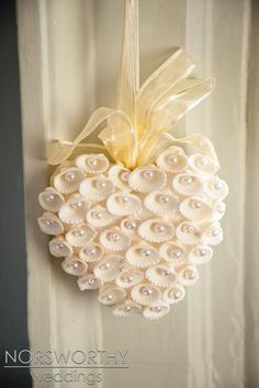 From pics of a wedding, but inspiration for a DIY.  A heart, some shells, some pearls, some gorgeous ribbon to make a bow and hanger. Sophisticated beach!