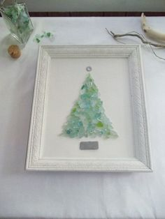 Soft turquoise beach sea glass tree on vintage canvas, set in vintage etched frame, painted soft creamy white. The base of tree is rectangle beach stone, topper is metal found on beach, and the tree is a collection of pale green and turquoise color beach glass. I cannot make these fast enough during the fall months. I've been commissioned to make many as gifts. I generally only make 4-5 originals per year, before running out of both glass and patience. In 2013, after depleting my green…