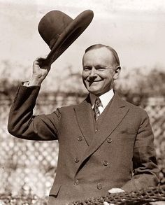 This photograph shows President Calvin Coolidge, tipping his hat to a crowd.