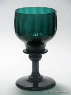 A superb Georgian Bristol green wine glass c1820 with a rib moulded double ogee bowl with a shoulder blade knop and swelling knop.