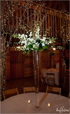 Large sprays of white flowers in tall, skinny vases    Photo by Jason