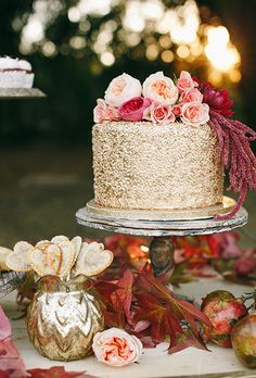 Brides.com: . A one-tiered metallic gold wedding cake topped with peach and pink roses, created by Sweet Art Bake Shop.