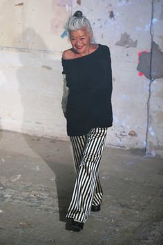 Slouchy black sweater tunic and black and white striped loose pants on fashion designer Junko Shimada at her runway show for Spring/Summer 2017. In 2016 at age about 57. (Shimada was born in 1959)